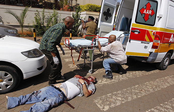 Rescuers attempt to evacuate a man injured in a shootout between armed men and the police at the Westgate shopping mall in Nairobi